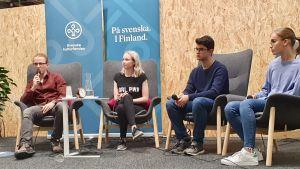 Två ungdomar sitter på stolar och deltar i en diskussion.