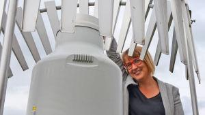 En ung kvinna står invid ett mätinstrument som ser ut som en mjölkbytta i metall.