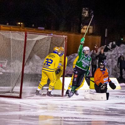 Två bandyspelare i gröna skjortor lyfter händerna i en segergest framför ett mål på en bandyplan. På bilden syns också spelare i gula och en orange skjorta.