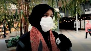 Kvinna med huvudduk och ansiktsmask blir intervjuad.