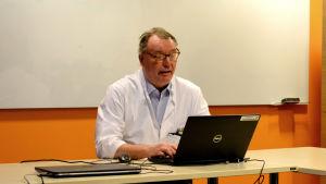 Man med glasögon och läkarrock sitter vid ett bord i ett mötesrum med en dator framför sig.