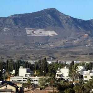 Stad och berg. På bergssidan ovanför staden har man fäst stora flaggor.