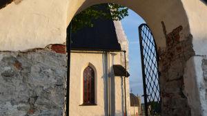 Genom kyrkporten syns en del av Borgå domkyrka i kvällssolen.