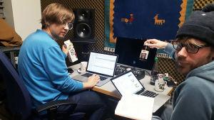 Kaksi Teakin opiskelijaa flunssaisina tietokoneidensa kanssa. Pöydällä on mustaherukkamehua, seinällä ryijy.