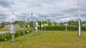 Flera mätinstrument i metall står på en gräsmatta.