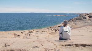Kvinna tittar ut mot horisonen på Åland