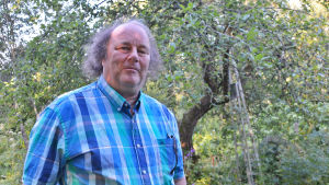 En man i blårutig skjorta står i en trädgård. Han tittar in i kameran.