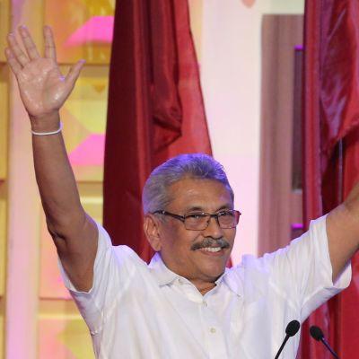 Gotabhaya Rajapaksa ler och sträcker upp händerna i luften.