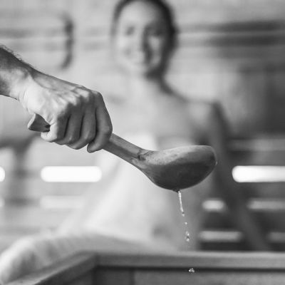 Mies kaataa vettä kiukaalle puukauhasta, sumeana taustalla näkyy lauteilla istuva nainen pyyhe päällään. Kuvassa Saunapäivän logo.