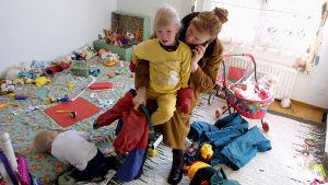Äiti puhuu kännykkään ja pukee samalla lastaan.