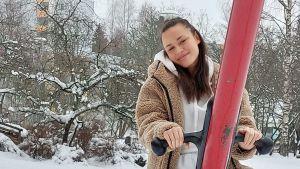 Kiara Nelson ler i kameran, sitter i en gunga, det är vinter, höghus i bakgrunden