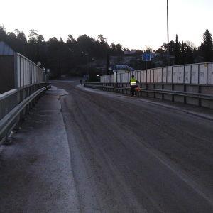 En bro för bilar och lätt trafik. Halt väglag. Mörk vintermorgon eller -kväll. En cyklist i reflexväst leder sin cykel på den smala trottoaren till höger. Klottrade räcken. Trafikmärke som visar att trafiken i ena riktningen har förkörsrätt.