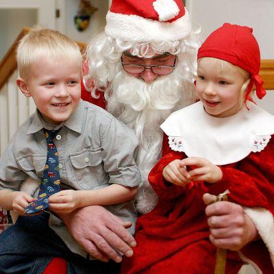 Lapset istuvat joulupukin sylissä.