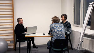 Kolme Teakin opiskelijaa istuvat huoneessa, jonka seinällä on fläppitaulu, puolapuut ja harmaa jumppapallo.