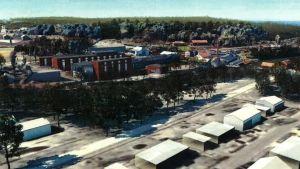 Bildmontage som visar hur nya stora hotellbyggnader kunde placeras i Billnäs bruk. Byggnaderna syns på andra sidan Svartån, den kännspaka skorstenen till höger.