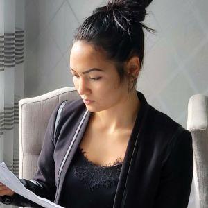 Nainen pitelee kädessään paperia.