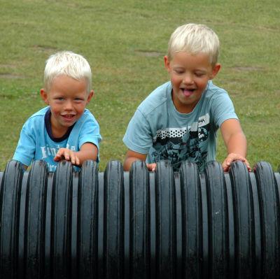 kaksi poikaa pyörittää mustaa isoa putkea