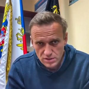 Aleksei Navalnyi katsoo vakavana kameraan. Hänellä on yllään sininen pusero, Taustalla huoneessa näkyy lippuja.ja ilmoitustaulu.