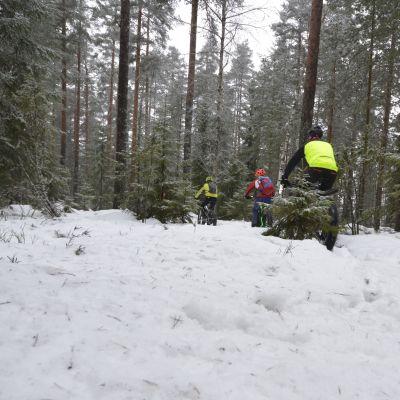 Maastopyöräilijöitä talvisessa metsässä