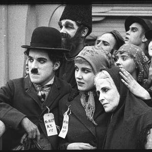 Charles Chaplin (vasemmalla) elokuvassa Siirtolainen (The Immigrant, 1917)