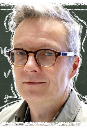 Kuvassa on Lappeen koulun rehtori Ville Laivamaa liitutaulun edessä. Taululla on aakkoset.