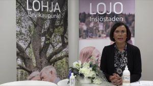 En kvinna i mörka kläder ser in i kameran och talar. I bakgrunden finns två affischer. Den ena står det Lojo på och det andra Lohja.
