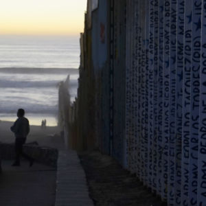 Muren som delar Mexico och USA. Ansikten och namn står inskrivna på muren. I bakgrunden syns en sandstrand och havet.