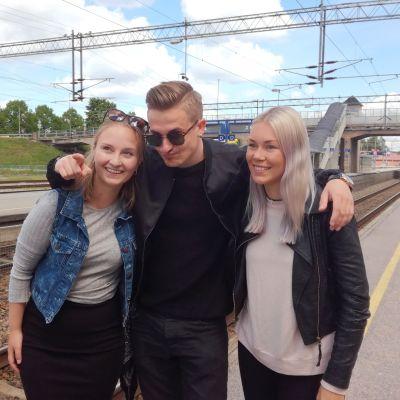 Tre unga vuxna poserar avslappnat på en järnvägsperrong. Det är två kvinnor och en man. Man ser räls och i bakgrunden en bro för biltrafik. Det är sommar..