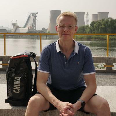 Kiinan curling-pelaajia valmentava Tomi Rantamäki poseeraa Pekingissä, taustalla näkyy freestyle- ja lumilautakisoja varten rakennettu big air -mäki.