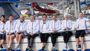 Nio kvinnor i vita jackor sitter i rad på en segelbåt och ler.