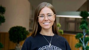 Porträtt av ung kvinna som ler och tittar in i kameran. Hon har en tröja där det står socionom.
