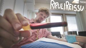 Toimittaja pitää kädessään näyteputkea, joka sisältää verta.