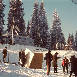 Puijolla lumisessa maisemassa tv-ulkolähetysauto ja tv-kamera sekä ihmisiä.  Tv-ulkolähetysauto 2 Puijon talvikisoissa vuonna 1962. Paavo Noponen ja Teija Sopanen keskustelemassa kuvan oikeassa alareunassa.