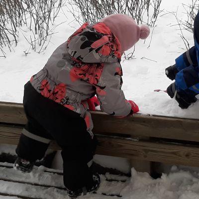 Två barn kryper över staket.