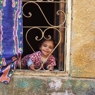 tyttö hymyilee ikkunassa