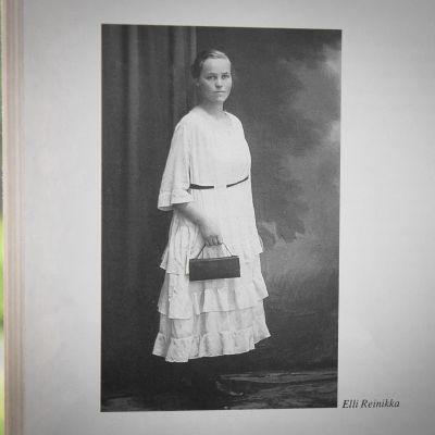 Nainen poseeraa mustavalkoisessa valokuvassa vakava ilme kasvoillaan. Yllä vaalea pitkä mekko, kädessä musta käsilaukku.
