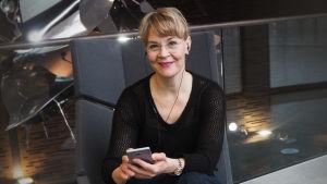 Kapellimestari Susanna Mälkki nappikuulokkeet korvissa.