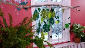 Ett insynsskydd gjort av gröna blad i filttyg hänger vid ett fönster