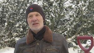 En äldre man i ett vinterlandskap.