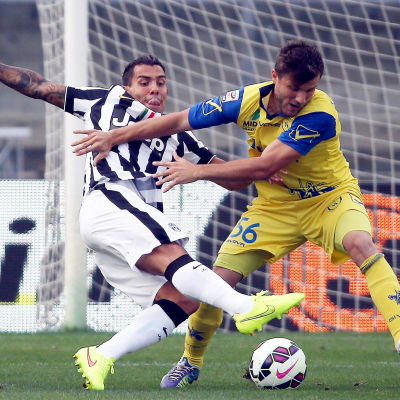 Juventus Carlos Tevez och ChievoVeronas Perparim Hetemaj i augusti 2014.
