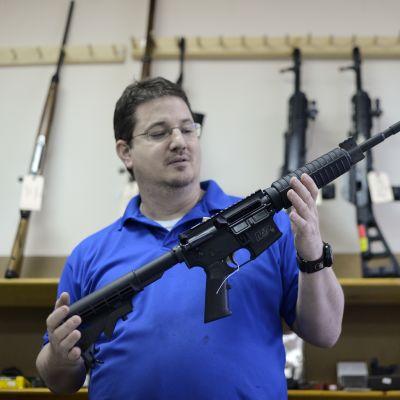 Asekauppias esittelee itselataavaa kivääriä