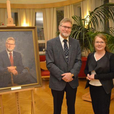 Ett porträtt av pensionerade stadsdirektören i Hangö Jouko Mäkinen. Bredvid tavlan står Mäkinen och konstnären Arja Järvilehto. I bakgrunden en stor grönväxt samt en julgran.