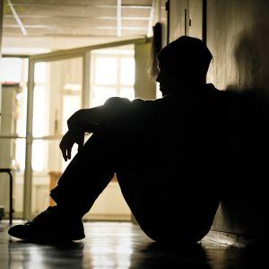 ungdom sitter ensam i en korridor