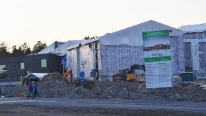 En byggarbetsplats invid en väg. Påen skylt står det Sipoonlahden koulu. Två personer och en hund går förbi medan skymningen håller på att lägga sig.