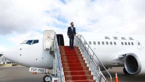 Kinas utrikesminister stiger ut från ett flygplan på flygplatsen i Ulan Bator.