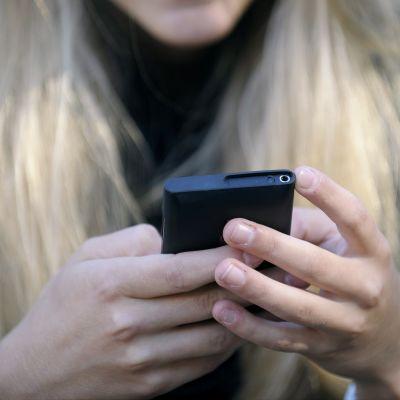 Tyttö käyttää matkapuhelinta.