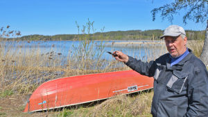 En äldre man står på en strand. Han ser in i kameran och pekar mot sjön med en pipa som han håller i handen.