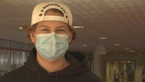 William Malkamäki, en ung man med munskydd, vit lippis bakfram och en svart munkjacka, står i en korridor.