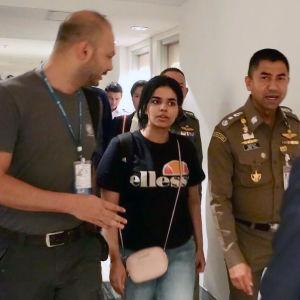 Rahaf al-Qunun tillsammans med en polis och en annan man.