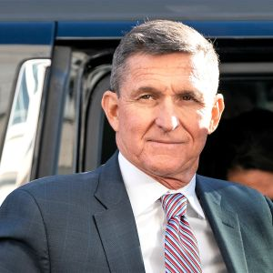 Michael Flynn seisoo auton vieressä puvussa ja kravatissa ja hymyilee vienosti,